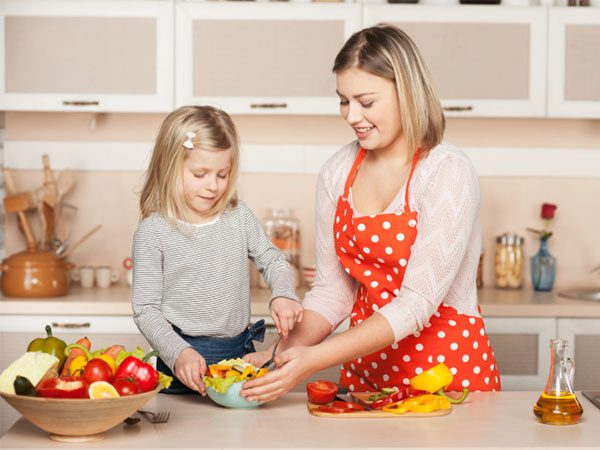 Smiling young mother and her little daughter cooking salad