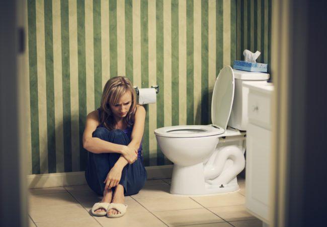 Sad young woman in bathroom